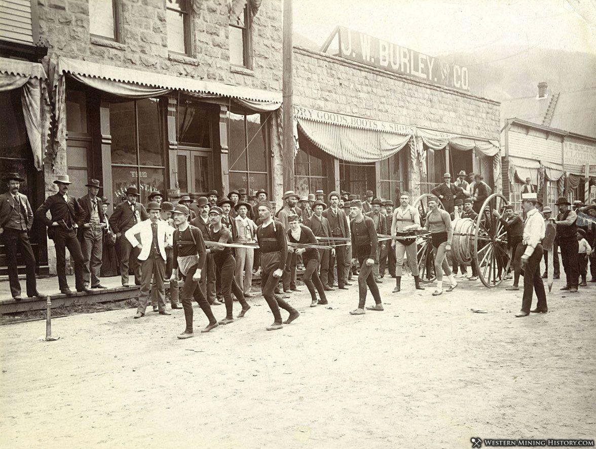 Firemen pull a hose cart at Rico circa 1890s
