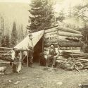Two Colorado Miners Pose in Front of Their Primitive Cabin