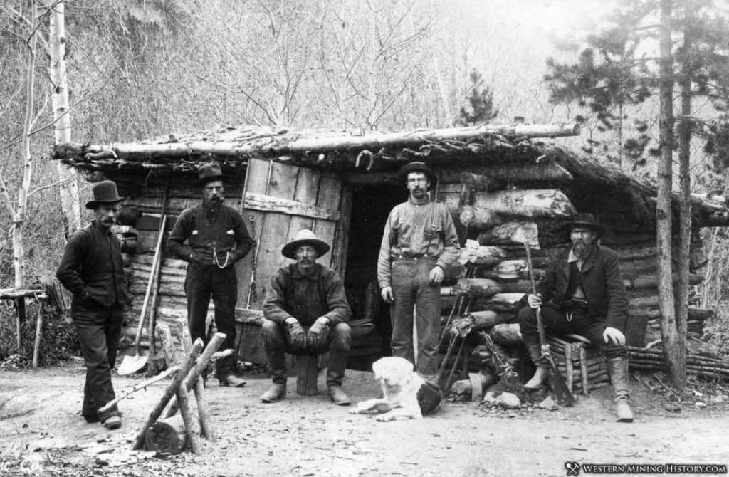 Miners pose with dog at their cabin somewhere in Colorado